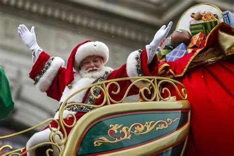 Santa, with a big smile,  in red sleigh with arms outstretched